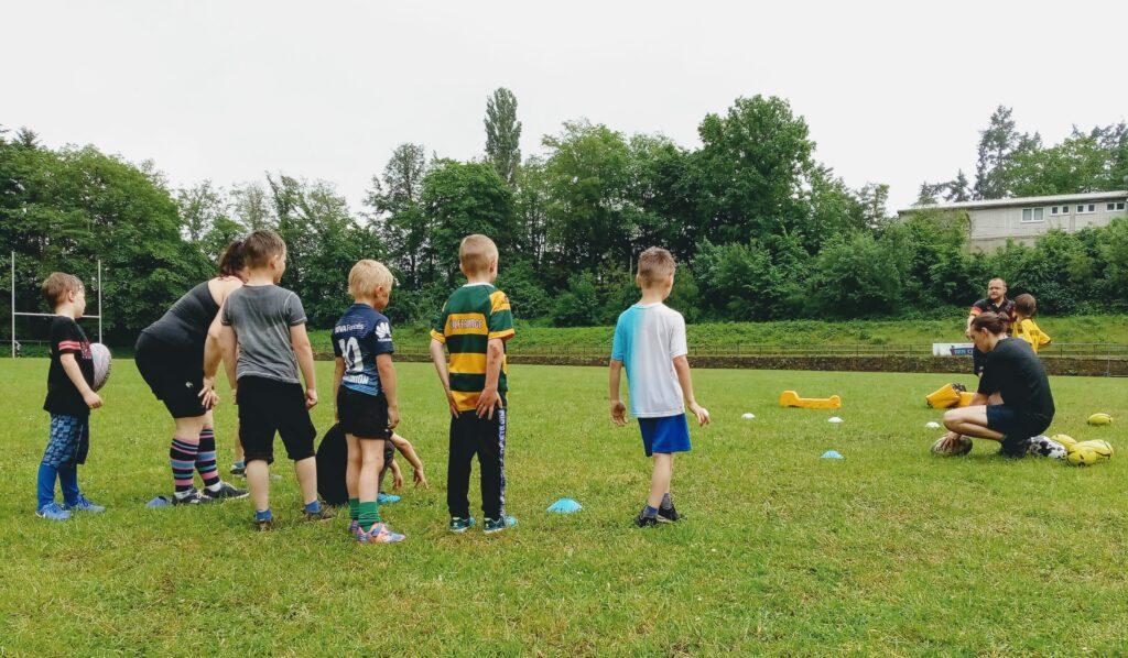 Gruppe von Kindern und Trainer*innen beim Rugbytraining im Waldstadion Trier.
