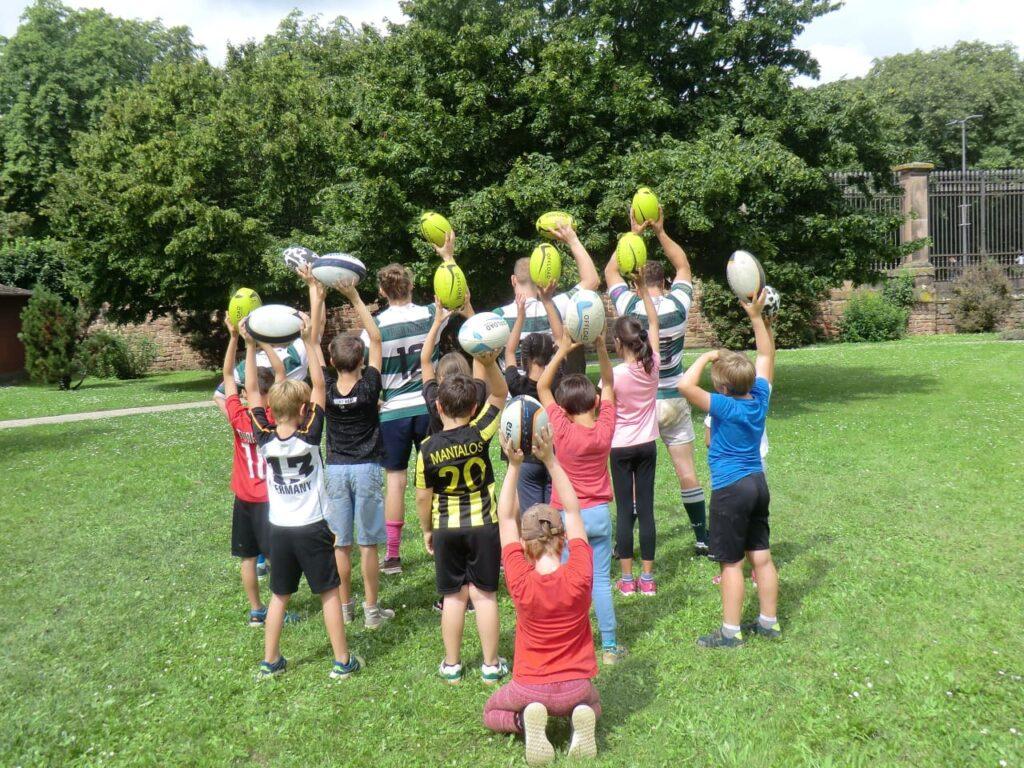 Kinder und Trainer:innen halten Rugbybälle in die Höhe.